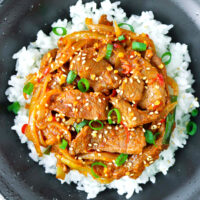 Close up top view of black bowl with spicy pork stir-fry on rice.