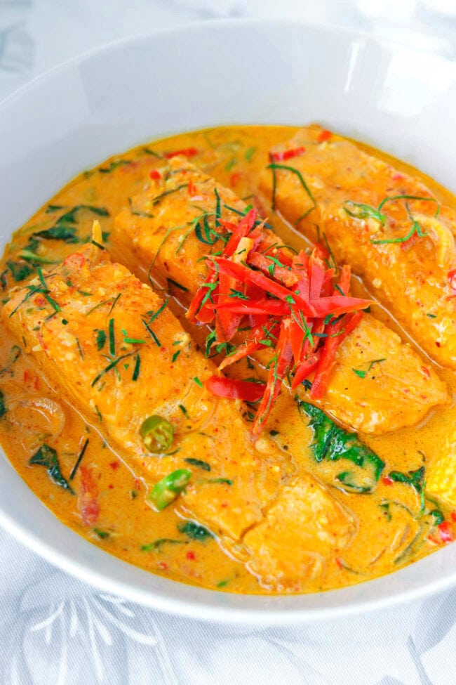 Front view of salmon fillets with choo chee red curry in bowl.