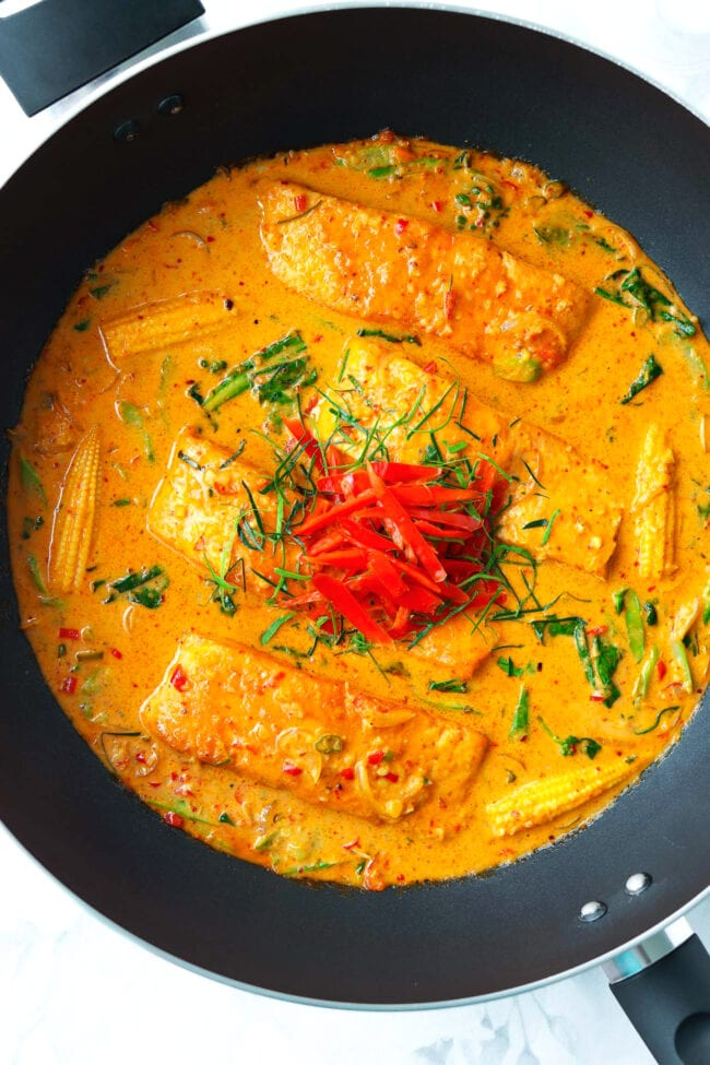 Four salmon fillets in choo chee red curry sauce in a wok.