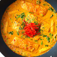 """Top view of Thai salmon thick red curry in a black. Text overlay """"Choo Chee Salmon Curry"""" and """"thatspicychick.com""""."""