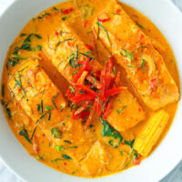 Top view of salmon fillets with choo chee red curry in a white round serving bowl.