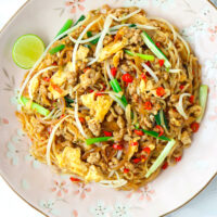 "Top view of plate with stir-fried noodles dish. Text overlay ""Pad Mee Korat"" and ""Pad Thai's Spicier Cousin""."