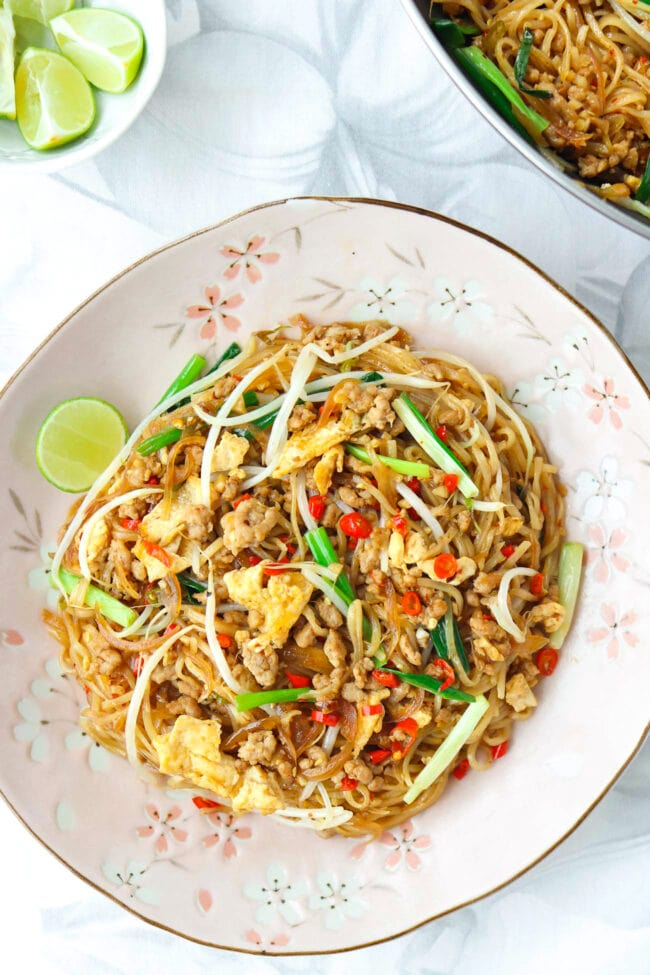 Top view of Thai stir-fried noodles dish on a plate with a lime wedge. Wok with stir-fry and small bowl with lime wedges behind.