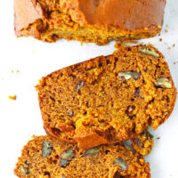 """Close up top view of loaf and two slices of bread on parchment paper. Text overlay """"Pumpkin Pecan Bread"""" and """"thatspicychick.com""""."""