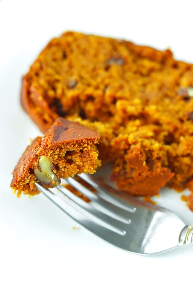 Close up of a fork on a plate with a bite of pumpkin pecan bread.
