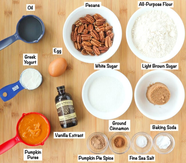Labeled ingredients for Pumpkin Pecan Bread on wooden board.