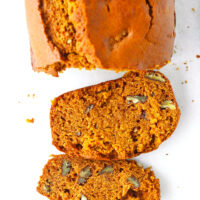 """Top view of loaf and two slices of bread on parchment paper. Text overlay """"Pumpkin Pecan Bread"""" and """"thatspicychick.com""""."""