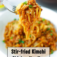 """Fork holding up a bite of noodles above plate with noodles. Text overlay """"Stir-fried Kimchi Chicken Noodles"""" and """"thatspicychick.com""""."""