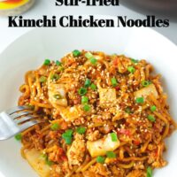 """Front view of plate with stir-fried spicy Korean noodles dish and a fork. Text overlay """"Stir-fried Kimchi Chicken Noodles"""" and """"thatspicychick.com""""."""