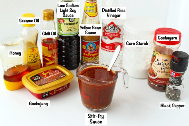 Labeled sauce ingredients for Stir-fried Kimchi Chicken Noodles and measuring cup with sauce and spoon on a white backdrop.