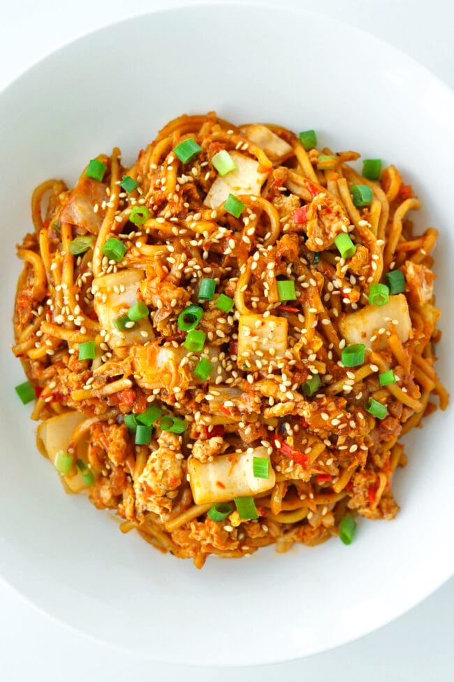 Close up top view of plate with stir-fried kimchi noodles.