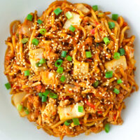 """Close up top view of plate with spicy Korean noodles dish. Text overlay """"Stir-fried Kimchi Chicken Noodles"""" and """"thatspicychick.com""""."""