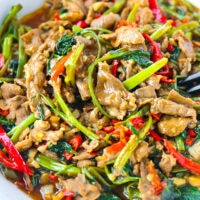 "Close up front view of bowl with lamb and veggies stir-fry. Text overlay ""Taiwanese Lamb and Water Spinach Stir-fry""."