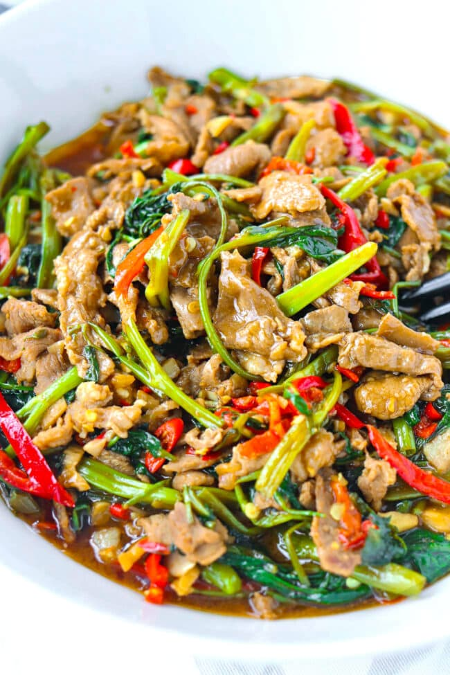 Close up front view of stir-fry lamb, water spinach, garlic, and chilies in a serving bowl.