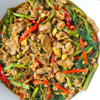 "Top view of bowl with lamb and veggies stir-fry. Text overlay ""Taiwanese Lamb & Water Spinach Stir-fry"" and ""With Sa Cha Sauce""."