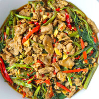 "Top view of bowl with lamb and veggies stir-fry. Text overlay ""Taiwanese Lamb and Water Spinach Stir-fry"" and ""thatspicychick.com""."