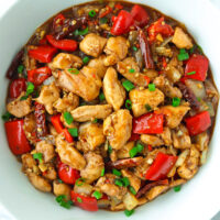 """Top view of bowl with a Chinese chicken, bell pepper, and onion stir-fry. Text overlay """" Spicy Pepper Chicken"""" and """"30 minute recipe""""."""