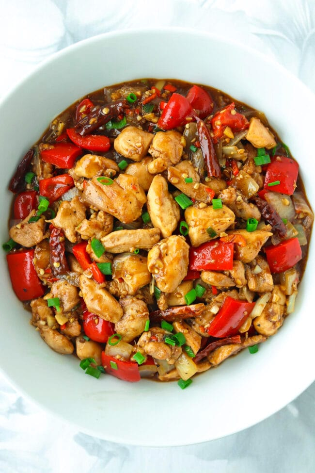Top view of bowl with a chicken, bell pepper, and onion stir-fry.