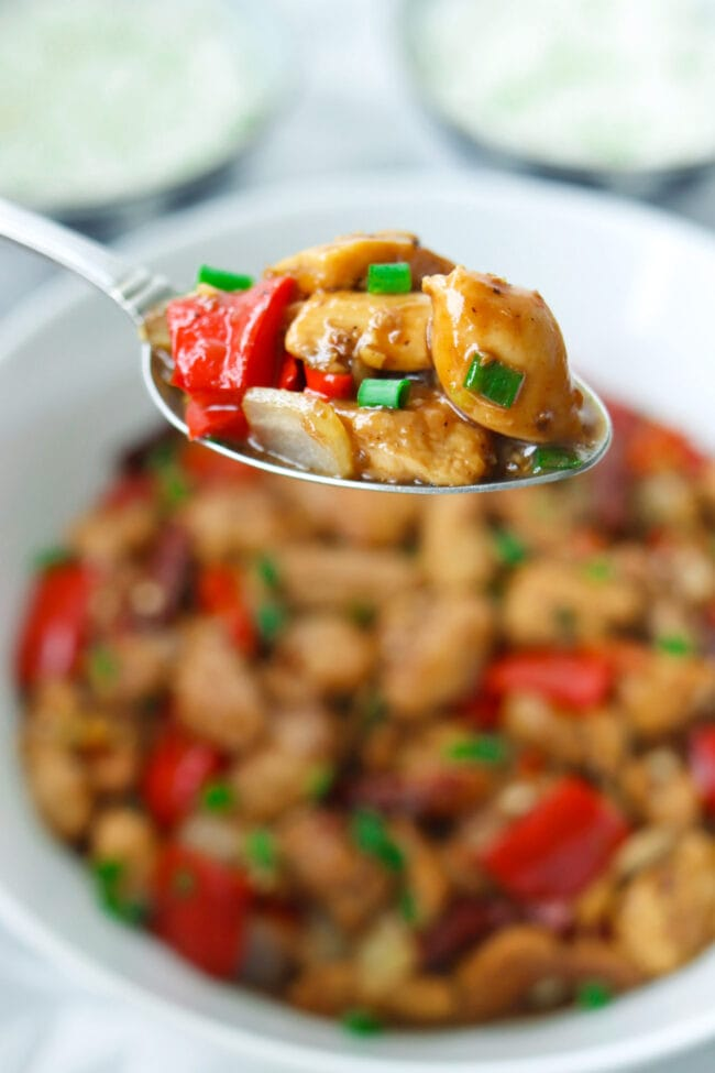 Spoon holding up a bite of chicken, bell pepper, and onion stir-fry.