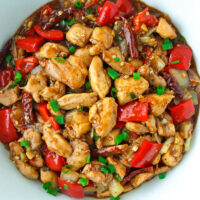 """Top view of a Chinese chicken stir-fry in a bowl. Text overlay """" Spicy Pepper Chicken"""" and """"thatspicychick.com""""."""