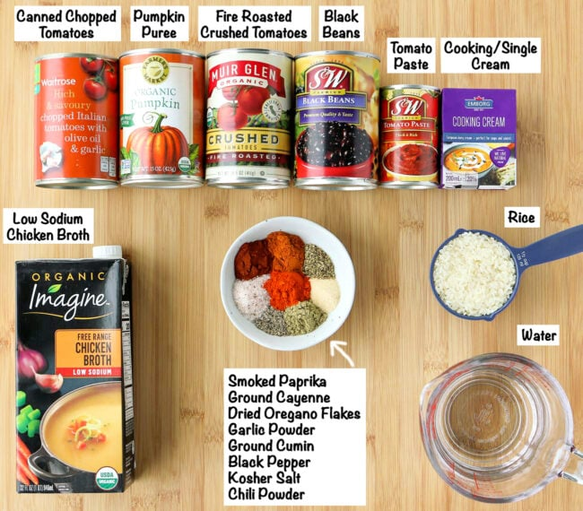 Labeled canned and pantry ingredients for Spicy Pumpkin Chicken Tortilla Soup on a wooden board.