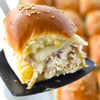 """Black spatula holding up a slider to show the layers of chicken salad, turkey, cheese, and cranberry sauce. Text overlay, """"Turkey & Chicken Cranberry Sliders"""" and """"thatspicychick.com""""."""