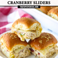 """Front view of three stacked sliders on plate, and sliders in a baking dish in the back. Text overlay, """"Turkey & Chicken Cranberry Sliders"""" and """"thatspicychick.com""""."""