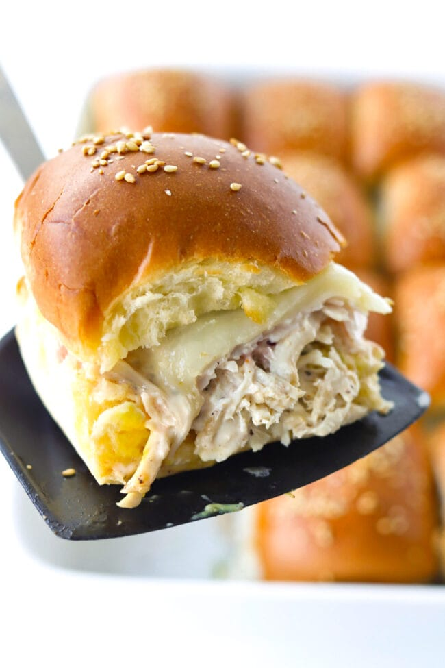 Spatula holding up a freshly baked slider to show the of layers chicken salad, turkey, cheese, and cranberry sauce.