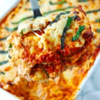 "Spatula pulling up a cheesy serving of ravioli lasagna from a baking dish. Text overlay ""Buffalo Chicken Ravioli Lasagna"" and ""thatspicychick.com""."