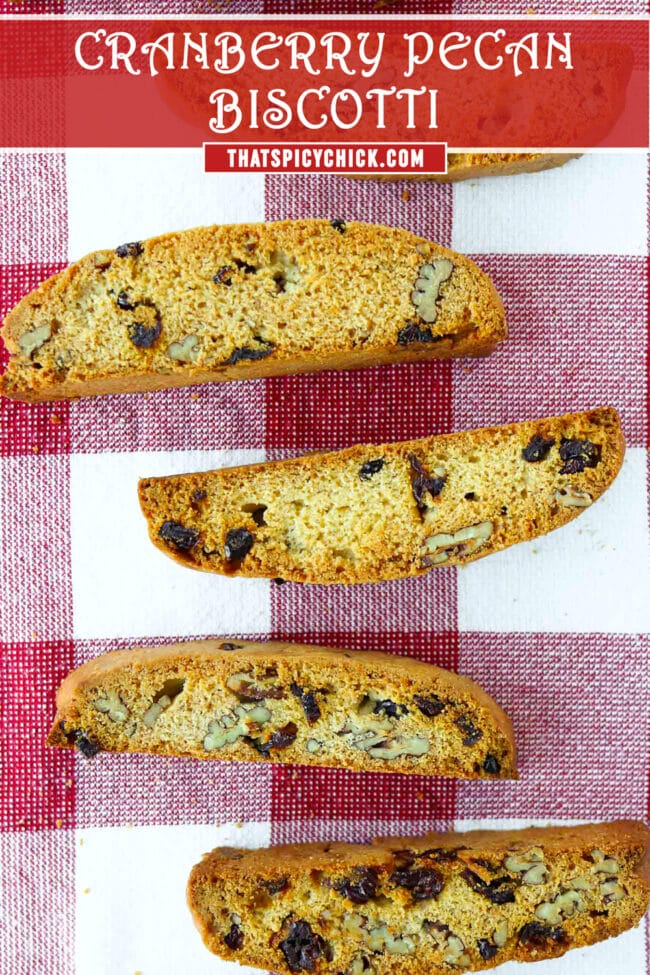 """Top view of five biscotti on a red and white checkered napkin. Text overlay """"Cranberry Pecan Biscotti"""" and """"thatspicychick.com""""."""