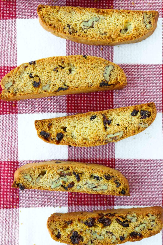 Top view of five biscotti on a red and white checkered kitchen napkin.
