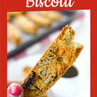 """Hand holding up a biscotti with a bite taken out. Text overlay """"Cranberry Pecan Biscotti"""" and """"thatspicychick.com""""."""