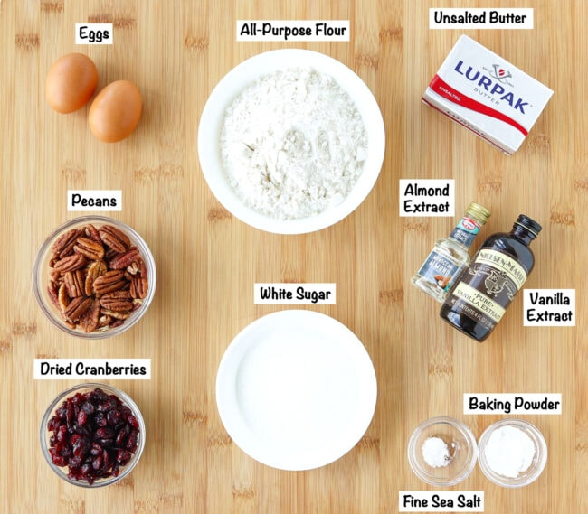 Labeled ingredients for Cranberry Pecan Biscotti on a wooden board.