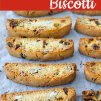 """Freshly baked biscotti on a parchment paper lined baking tray. Text overlay """"Cranberry Pecan Biscotti"""" and """"thatspicychick.com""""."""