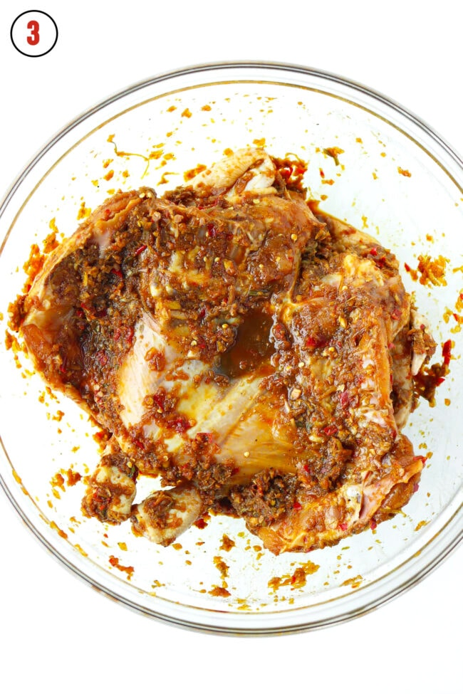 Spatchcocked chicken in large mixing bowl with marinade.
