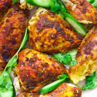"""Close-up of chicken pieces on platter with cucumber and coriander. Text overlay """"Spicy Thai Roast Chicken"""", """"thatspicychick.com"""" and """"with Spicy Dipping Sauce (Nam Jim Jaew)""""."""