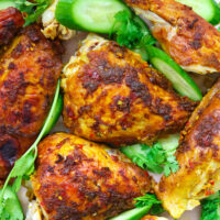 """Close-up of chicken pieces on platter with cucumber and coriander. Text overlay """"Spicy Thai Roast Chicken"""" and """"thatspicychick.com""""."""