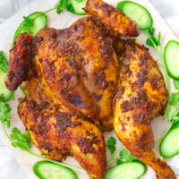 """Roast chicken on platter with cucumber and coriander. Text overlay """"Spicy Thai Roast Chicken"""" and """"thatspicychick.com""""."""