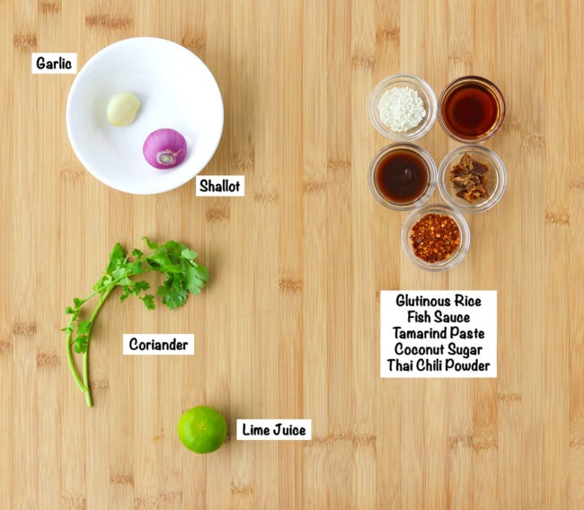 Labeled ingredients for Nam Jim Jaew (spicy dipping sauce) on a wooden board.