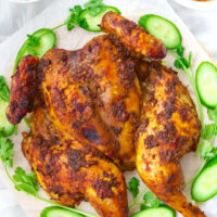 """Top view of whole roast chicken on platter with cucumber and coriander. Text overlay """"Spicy Thai Roast Chicken with Spicy Dipping Sauce"""" and """"thatspicychick.com""""."""
