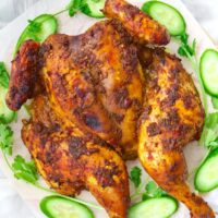 """Top view of whole roast chicken on a platter with cucumber slices and coriander sprigs. Text overlay """"Spicy Thai Roast Chicken"""" and """"thatspicychick.com""""."""