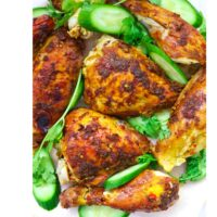 """Cut chicken pieces on a platter with cucumber slices and coriander sprigs. Text overlay """"Spicy Thai Roast Chicken"""" and """"thatspicychick.com""""."""