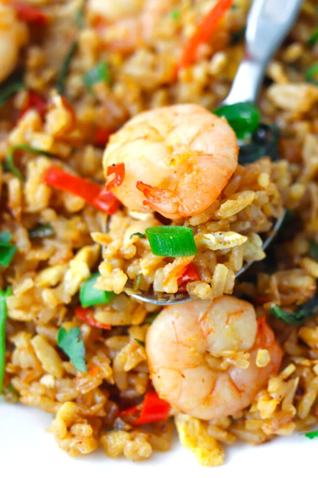Close up of fried rice with prawn on a spoon on a plate.