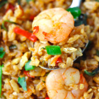 """Close up of spoon with fried rice and a prawn on a plate. Text overlay """"Thai Roasted Chili Fried Rice with Prawns"""" and """"thatspicychick.com""""."""