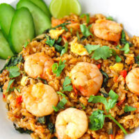 """Front view of spicy prawn fried rice on a plate. Text overlay """"Thai Roasted Chili Fried Rice with Prawns"""" and """"thatspicychick.com""""."""