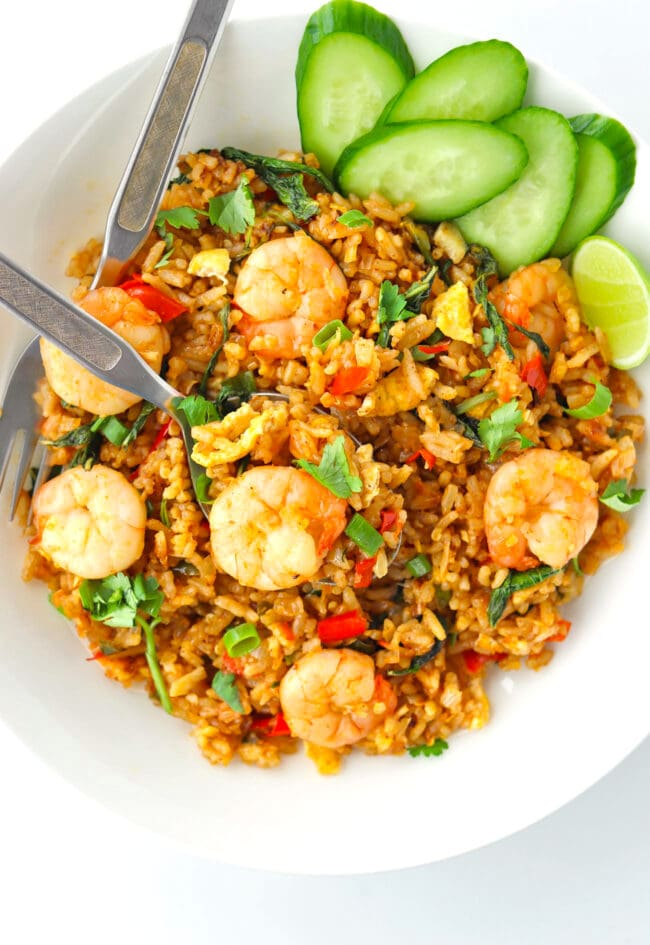 Top view of plate with spicy prawn fried rice on a plate with a spoon, fork, cucumber slices, and a lime wedge.