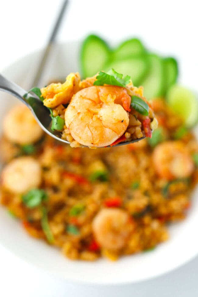 Spoon holding up a bite of fried rice with a prawn.