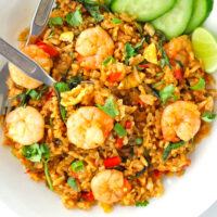 """Spicy prawn fried rice on a plate with a fork and spoon. Text overlay """"Thai Roasted Chili Fried Rice with Prawns"""" and """"thatspicychick.com""""."""