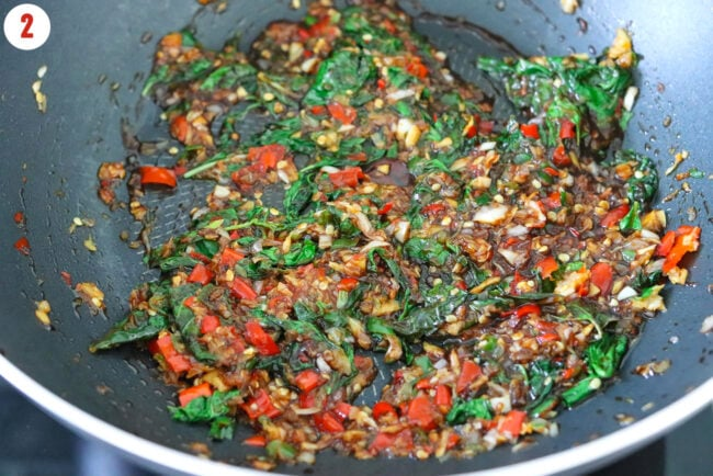 Stir-fried shallots, garlic, chilies, Thai holy basil, and sauces in a wok.