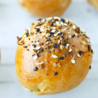 """Front view of bagel bomb with Everything Bagel Seasoning. Text overlay """"Greek Yogurt Dough Stuffed Bagel Bombs"""" and """"thatspicychick.com""""."""